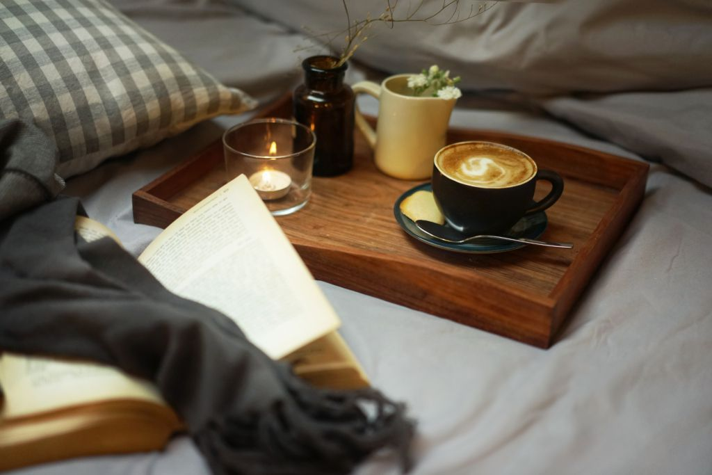 Cappuccino on a bed-top tray, with a book.