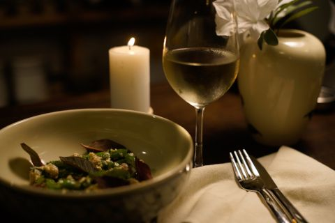 A glass of white wine illuminated by candlelight, Summer Salad in foreground.